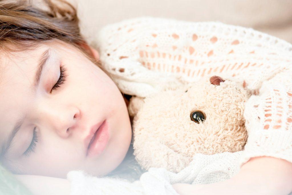 Autistic child sleeps with teddy bear