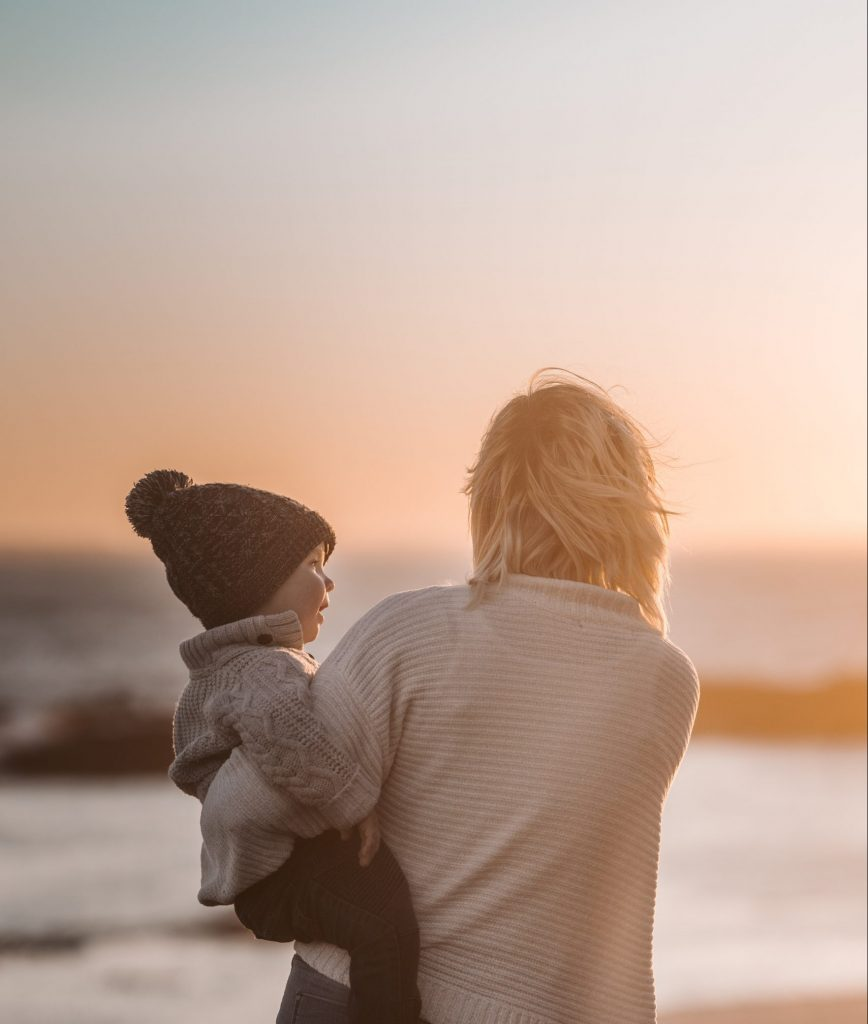 Mother carries autistic child near the ocean at sunset