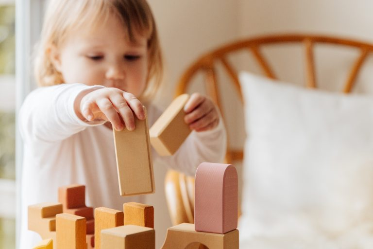 A child stacks blocks as a form of ABA therapy for autism