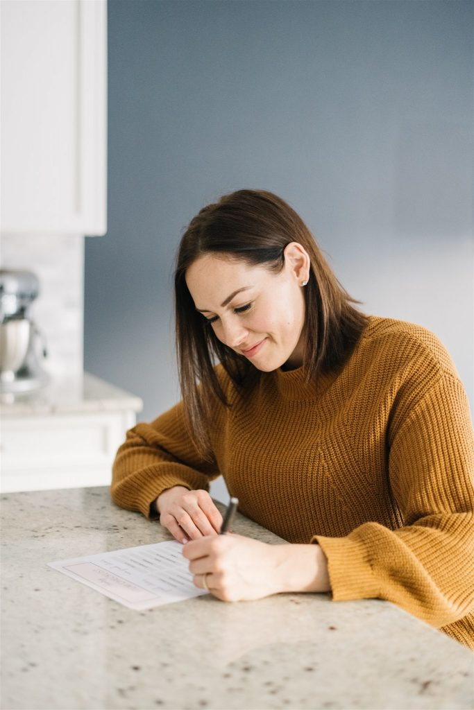 woman sits at kitchen counter making list of goals as a form of self care for mothers