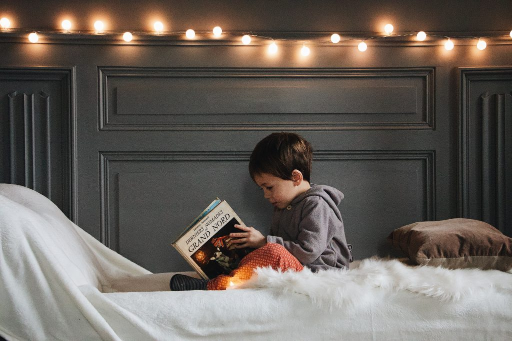 a child reads a book in bed