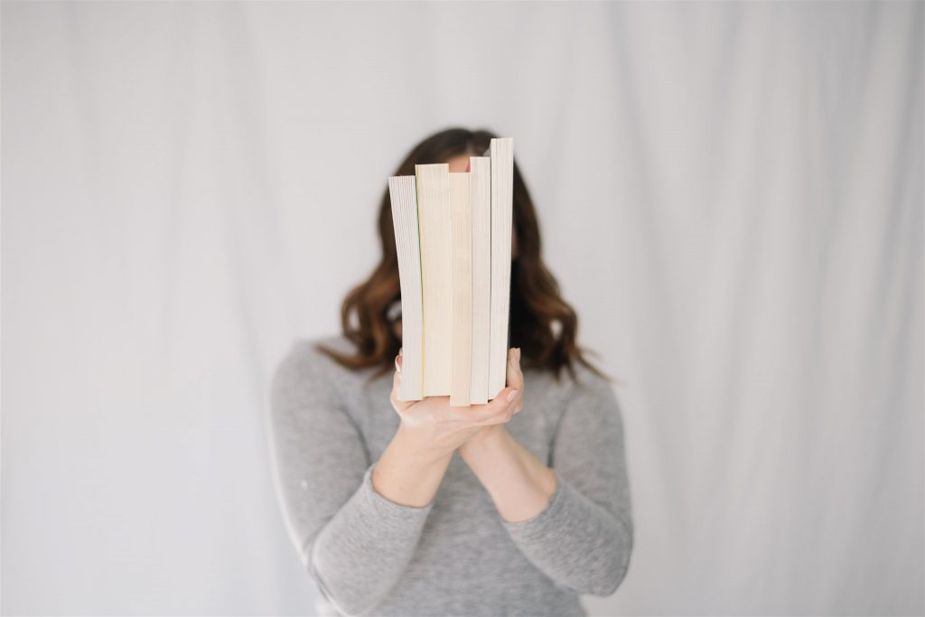 Woman holds a row of books in front of her face with the jackets facing away from the camera