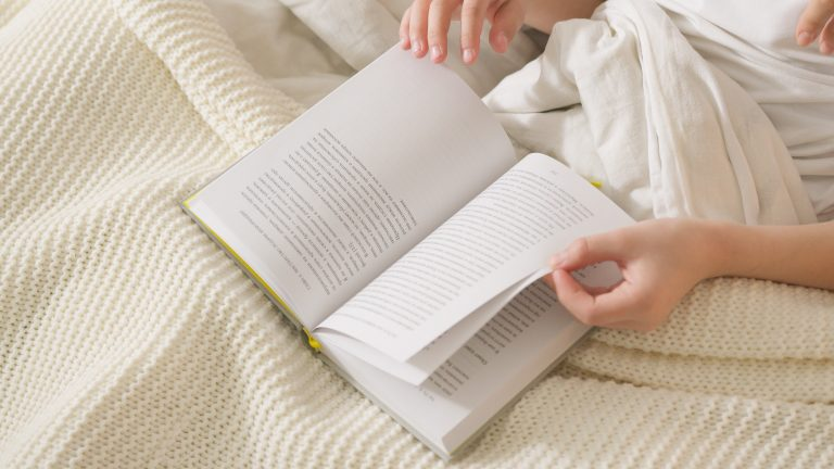 respectful parenting book list, woman's hands on an open book while she sits in bed under a cream coloured knit blanket
