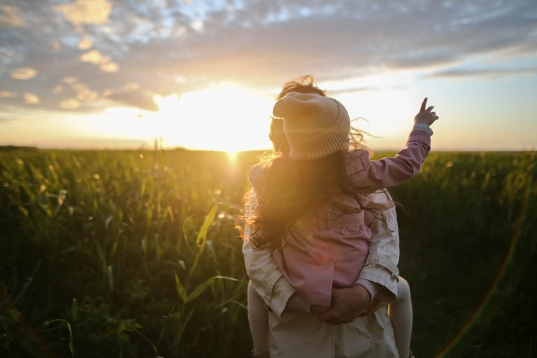 a mother holds her child in her arms in a field at sunset