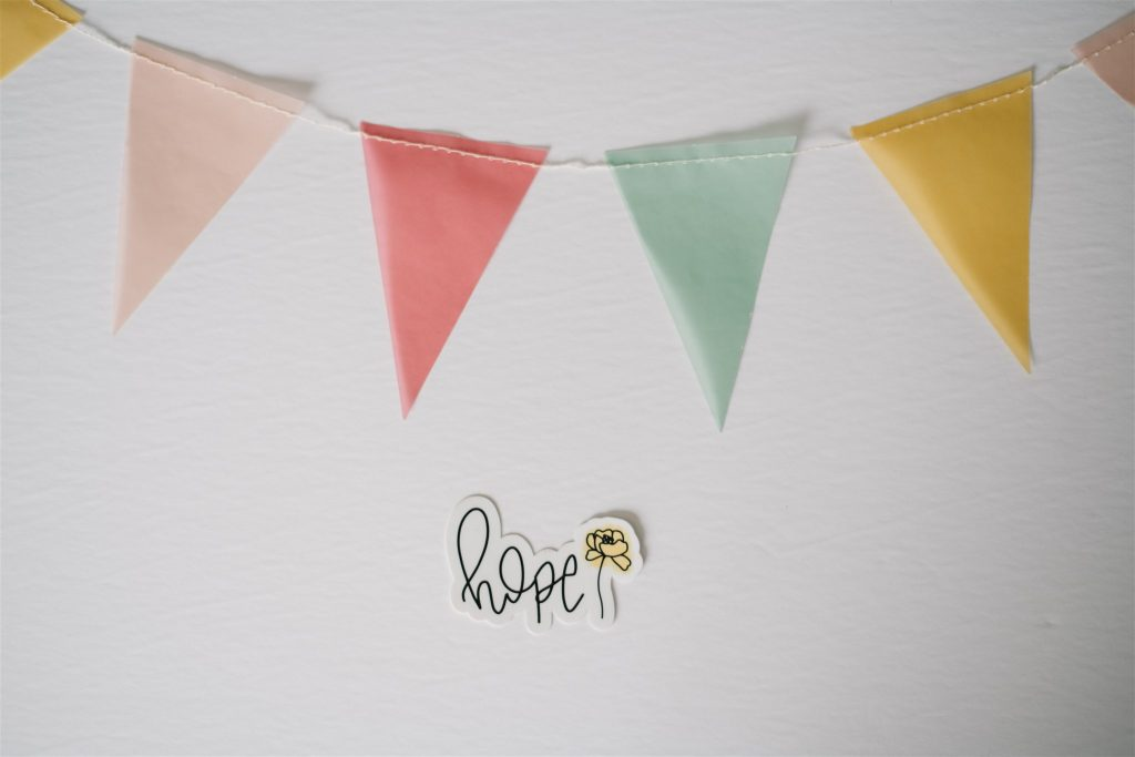 """a small colourful banner with triangle shaped pennants hang above a little calligraphy that says """"hope"""" with a hand drawn flower beside"""
