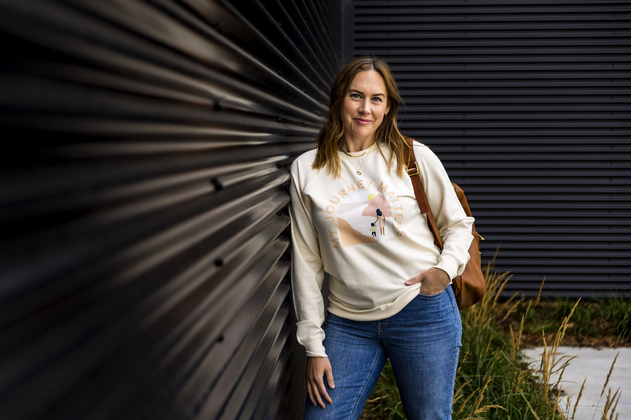 """woman leans agains black wall, wearing cream coloured crewneck with an illustration of mother and child walking down a path with the headline """"my journey matters"""""""
