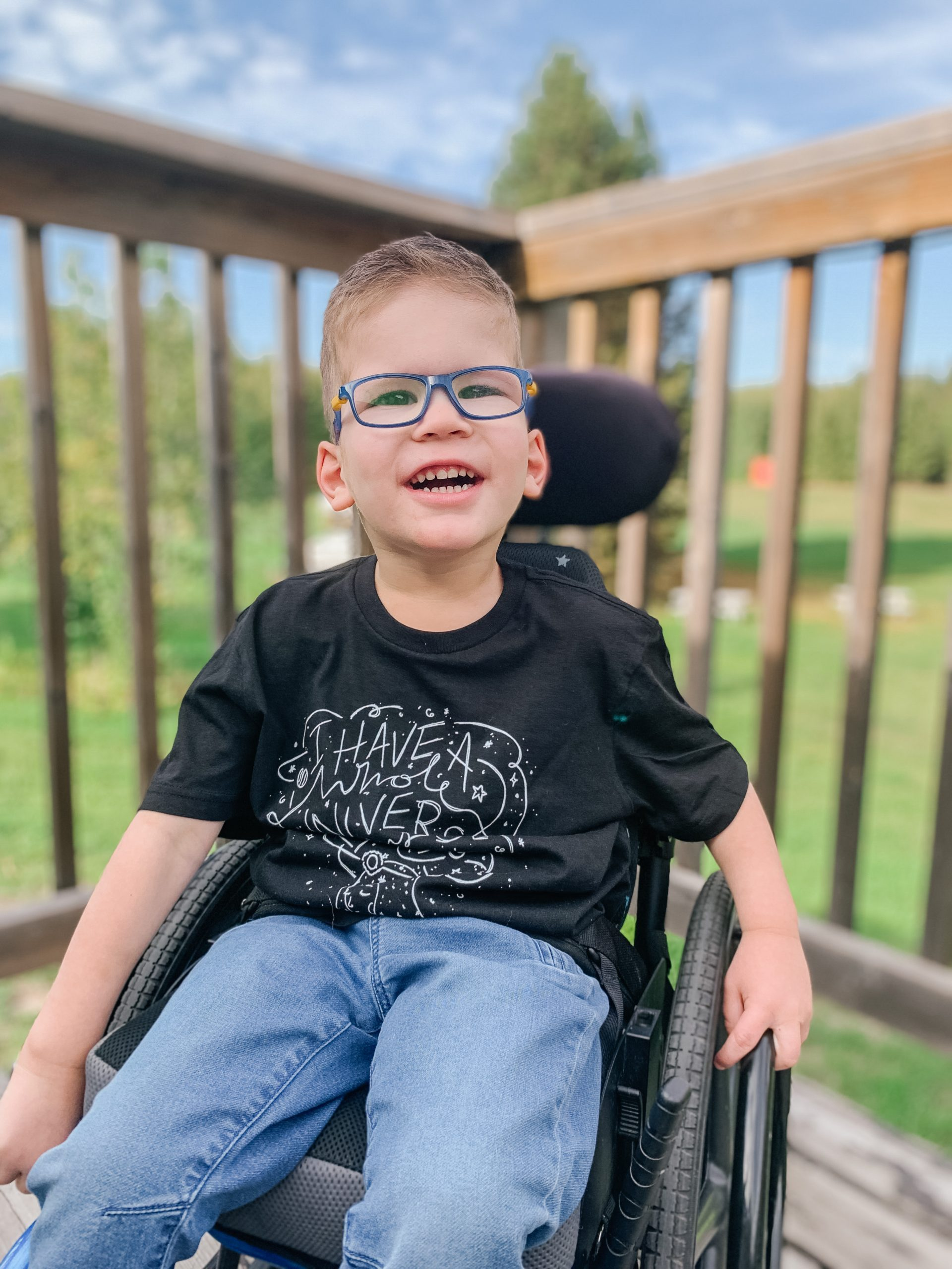 """preschool aged boy sits in his wheelchair wearing a shirt that says """"I have a whole Universe in my mind"""" to showcase that though he is nonspeaking, he has thoughts and ideas that he would love the opportunity to communicate"""